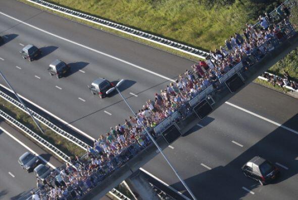 Esta foto aérea muestra a decenas de personas mirando pasar a un convoy...