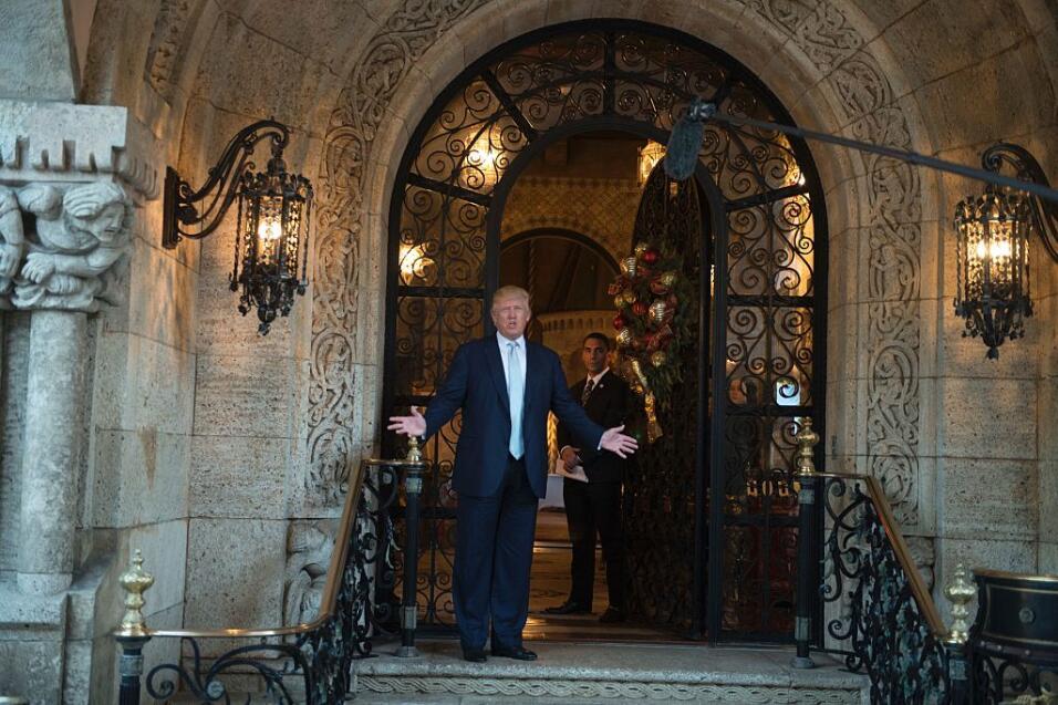 Donald Trump se dirige a los periodistas desde el pórtico de su mansión...