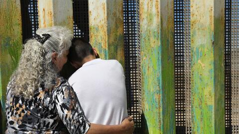 Una abuela y su nieto se abrazan mientras conversan con familiares al ot...