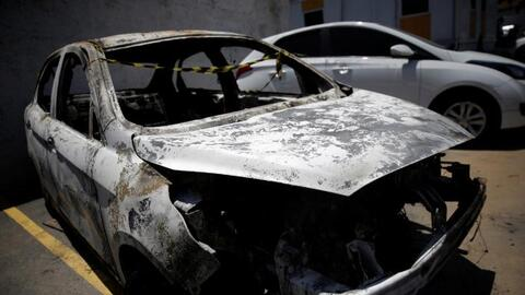 A burned car in which a body was found during searches for the Greek Amb...