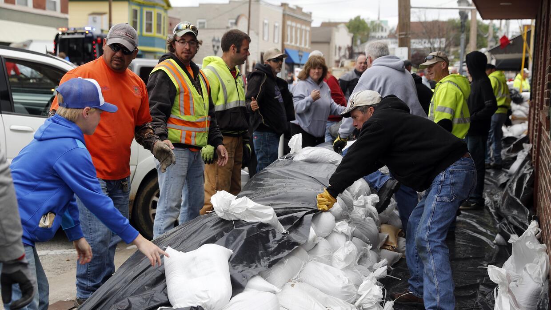 Los vecinos de Eureka, Missouri, recogen sacos de arenas para protegerse...