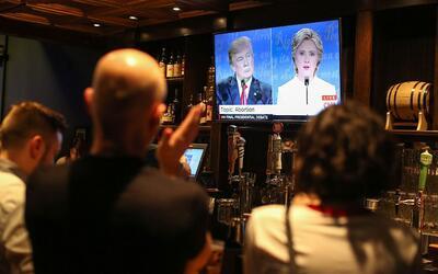 Un grupo de televidentes presencia el debate presidencial final en una t...