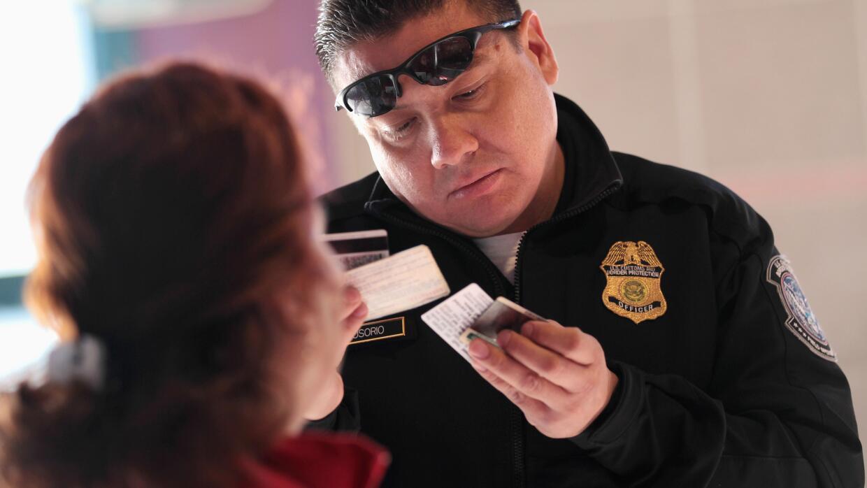 Un agente de inmigración de EEUU revisa los documentos de un inmi...
