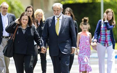 Dr. Salomon Melgen holds hands with his wife, Flor, as he leaves the fed...