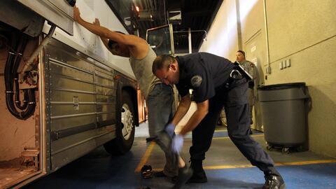 Un indocumentado es revisado por un agente de ICE.