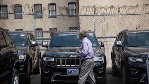 Un cliente inspecciona los vehículos en el patio de ventas de un...