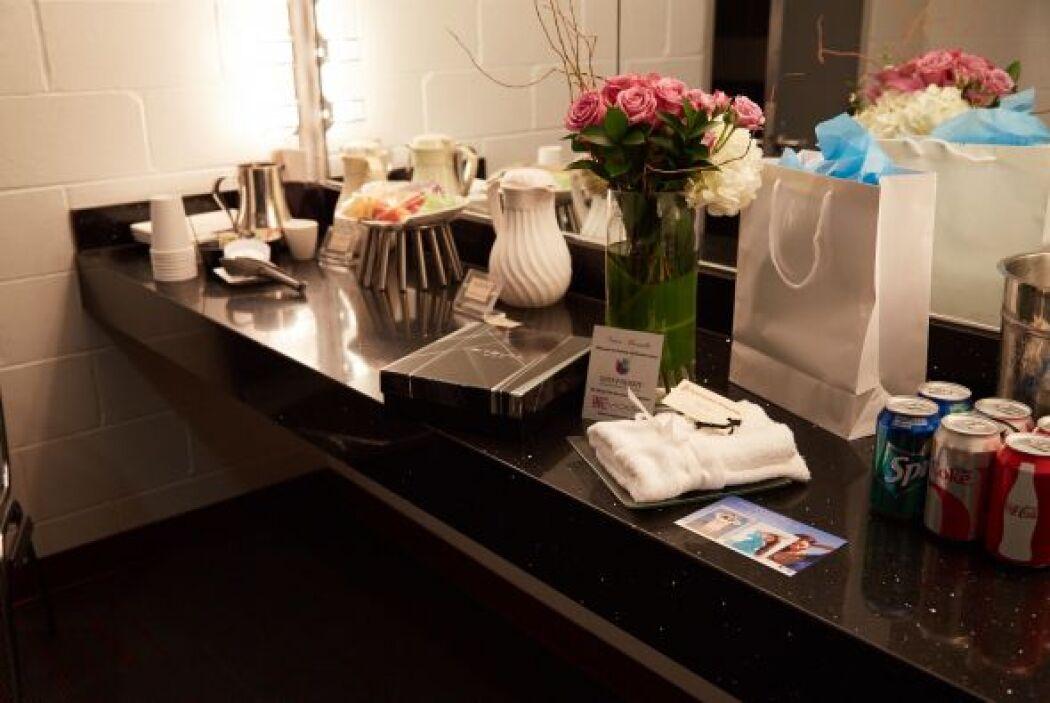 Unas flores y sus regalos destacan frente al espejo.