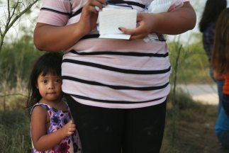 La niña hondureña Laura Fabio, de 2 años, junto a su madre tras cruzar e...