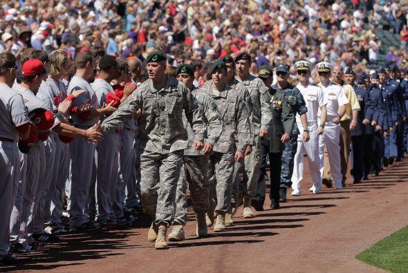 Los jugadores saludaron a los soldados que marchaban por el campo.