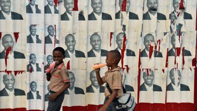 Unos niños pasan delante de carteles electorales.