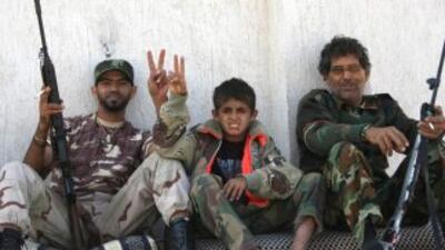 Combatientes del CNT descansan en una calle de Sirte, el pueblo natal de...