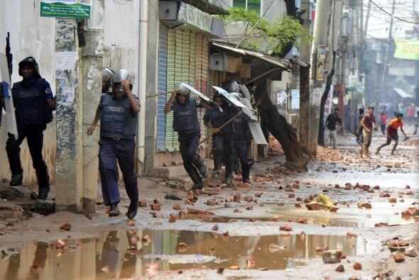Funcionarios de la policía de Bangladesh se cubren de las piedras...