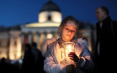 Una niña enciende una vela durante una vigilia en la Plaza de Tra...