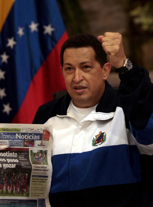 Venezuela's President Hugo Chavez gestures as he holds a newspaper s...