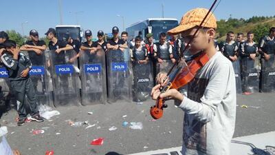 Niño refugiado sirio toca el violin frente a barricada de la policía
