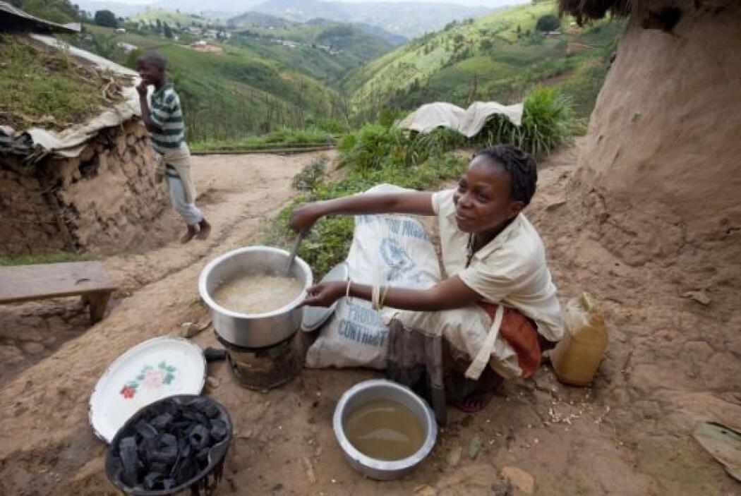 Nikuze Aziza cuece el maíz sobre una pequeña estufa afuera de su casa en...