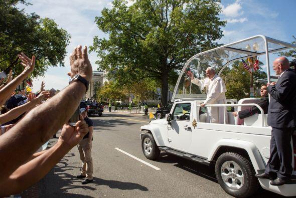 Las manos saludando al pontífice que viaja en el Papamóvil.