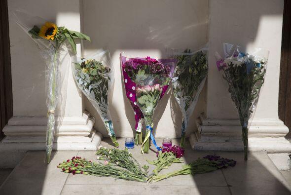 Varias personas también llevaron flores y encendieron velas frente a la...