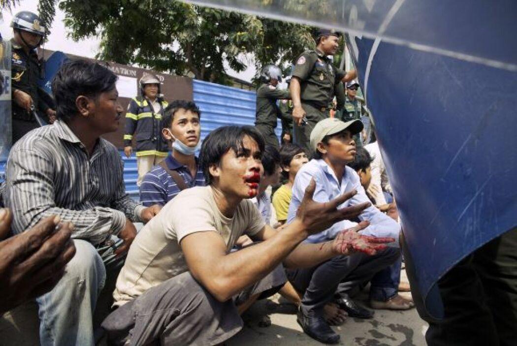 Los manifestantes se sientan en el suelo después de haber sido detenidos...