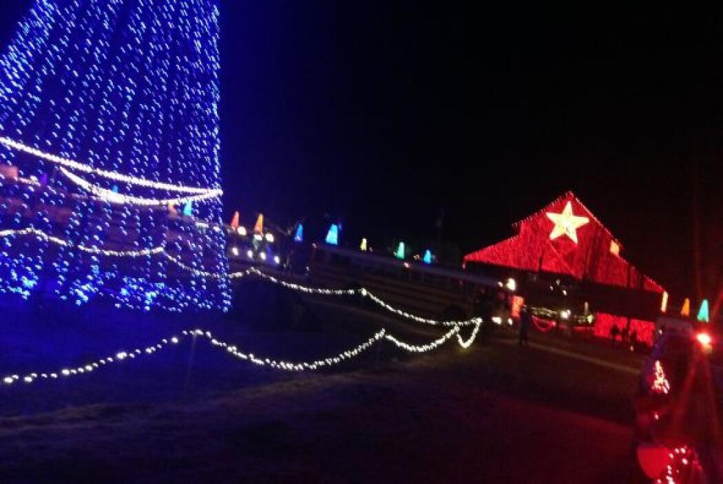 En la entrada, una casa de madera completamente cubierta de luces recibe...