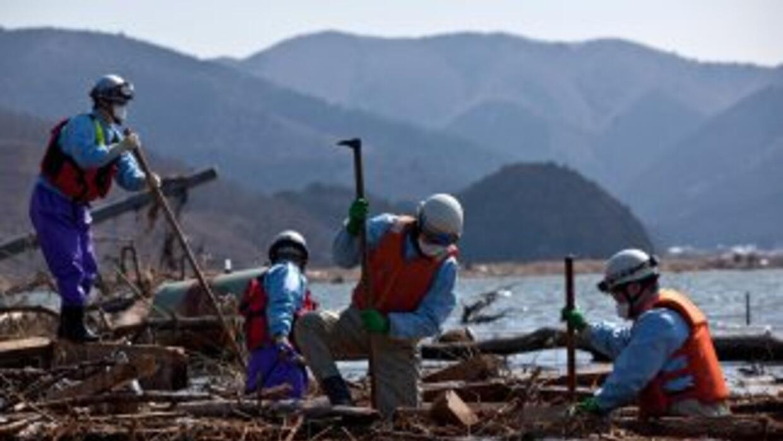 Trabajadores y rescatistas buscan cadáveres en la costa de Fukushima, de...