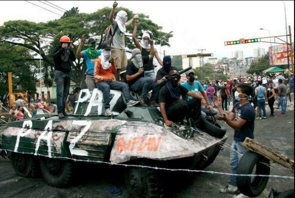 Jóvenes protestan a bordo de una tanqueta de la policía en...