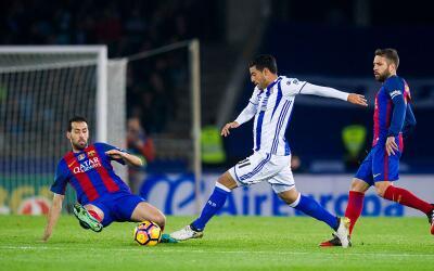Carlos Vela intenta tirar ante una barrida de Sergio Busquets.