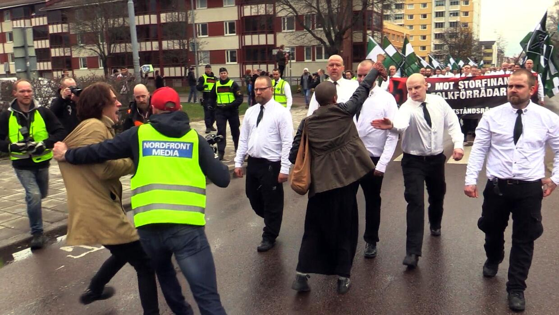 Tess Asplund alzando su puño frente a una marcha de partidarios d...