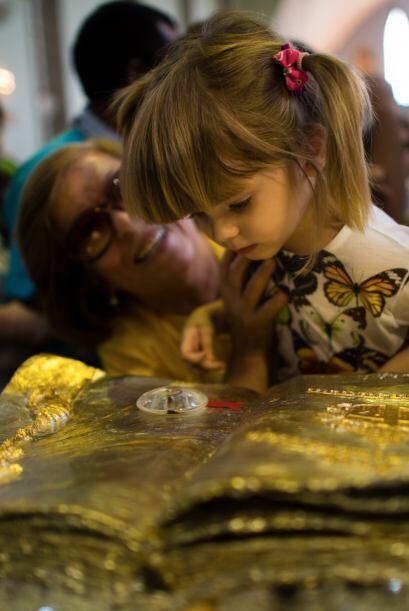 Una niña mira la reliquia oficial del beato Juan Pablo II. Su madre sonr...
