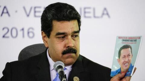 Venezuela's President Nicolas Maduro holds a book with a photo of Venezu...