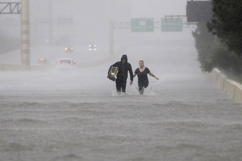 Two people on a flooded section of Interstate 610 in floodwaters from Tr...
