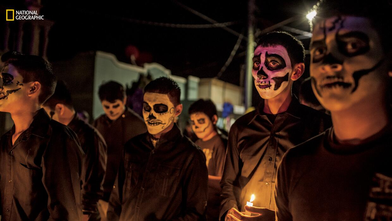 Residentes de Allende, con las caras pintadas de calaveras, participan e...