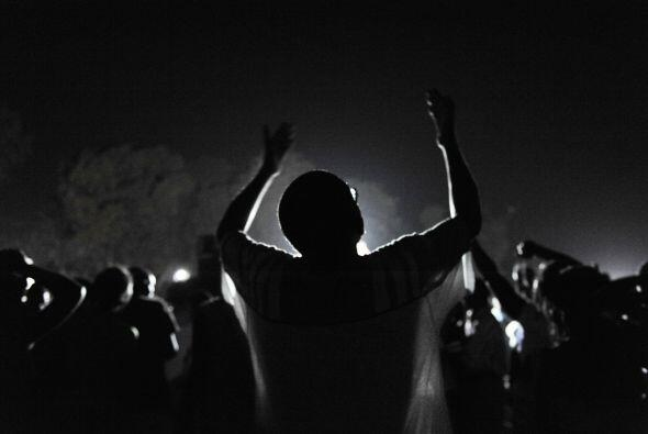Las siluetas se vislumbran en la oscuridad de la noche, marchando desde...