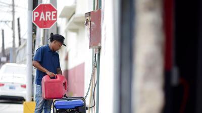 Un joven pone gasolina en un generador eléctrico.