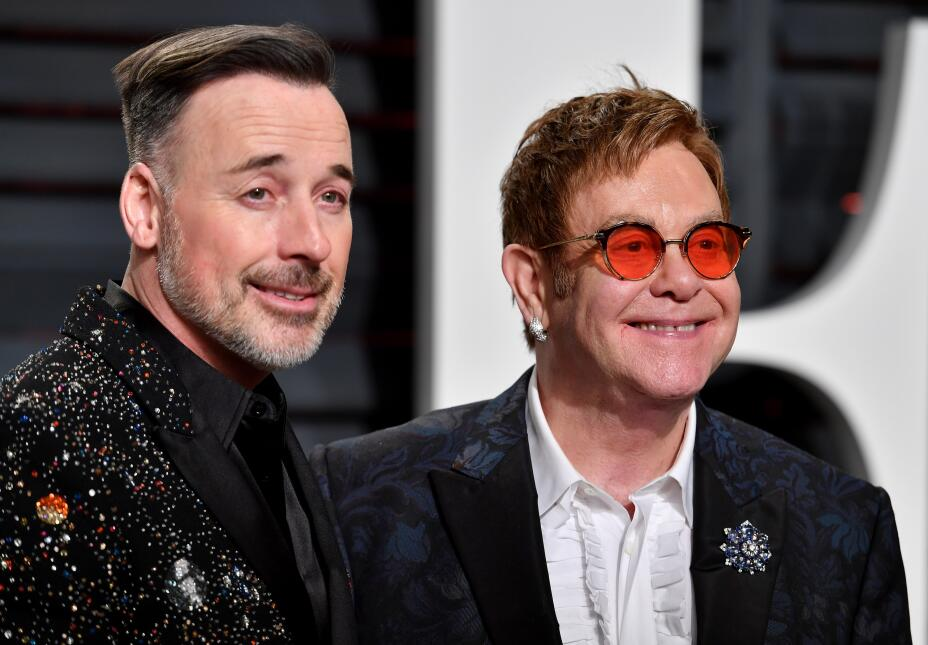 Director-producer David Furnish (L) and recording artist Elton John atte...