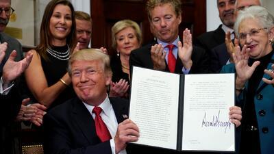 El presidente Trump sonríe al firmar una orden ejecutiva que permitirá c...