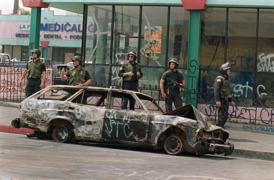 Cinco efectivos de la Guardia Nacional frente a un coche vandalizado.
