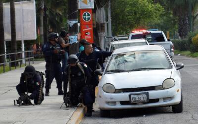 Policías se resguardan detrás de un vehículo durant...