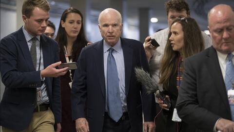 El senador John McCain rodeado de reporteros.