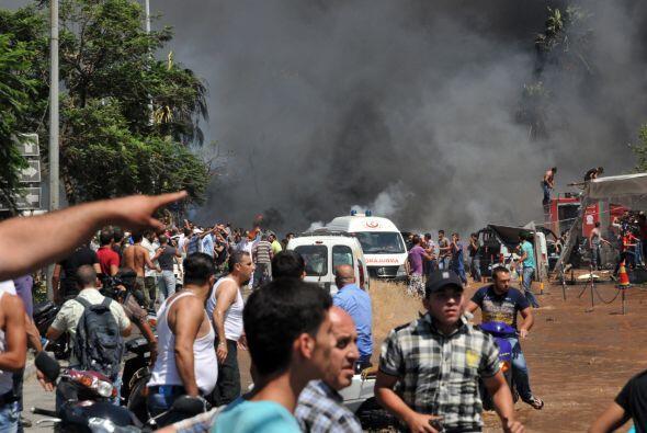 Se ven automóviles calcinados, personas heridas o muertas que yacen en l...