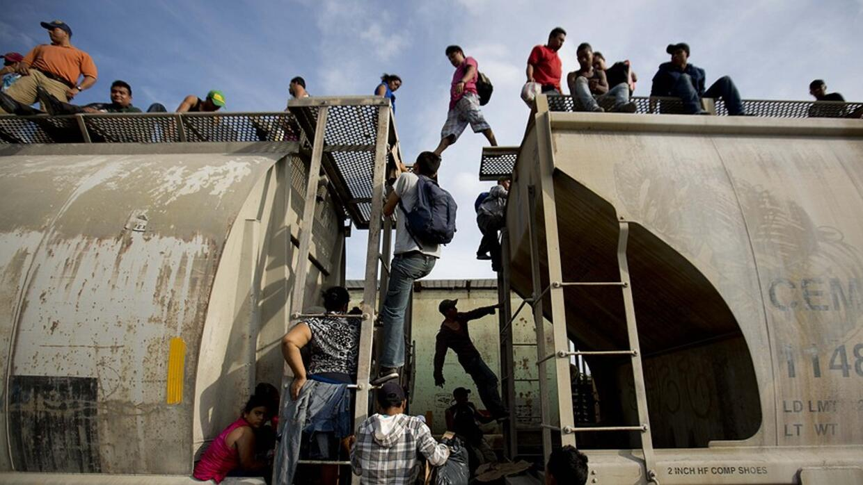 Central American migrants climb on a train during their journey toward t...