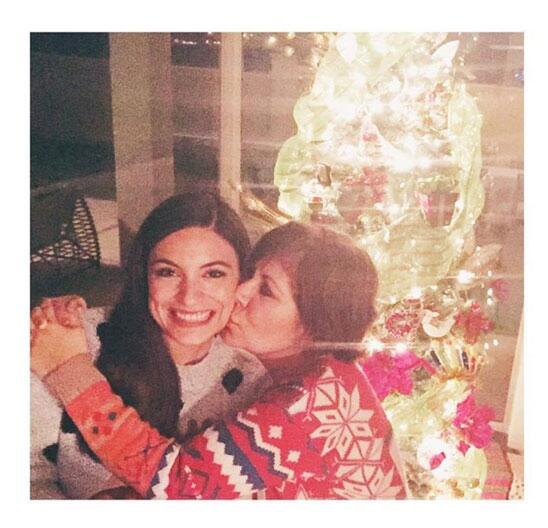 Ana Brenda Contreras recibe un beso de su mami frente al arbolito.