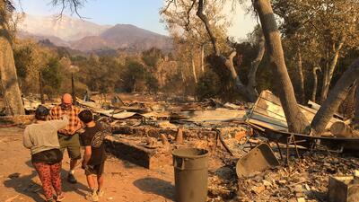 Jake Colborn y sus nietos recorren los escombros de su casa, que quedó t...
