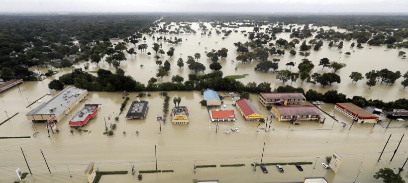 El agua que se escapa del reservorio Addicks fluye sobre los vecindarios...