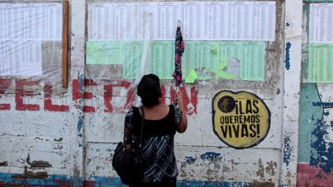 Una mujer busca su nombre en una lista de votantes habilitados para las...