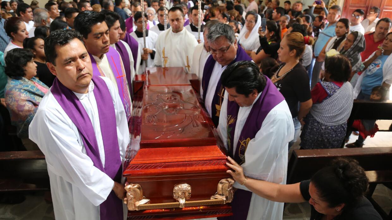 Sacerdotes llevan el ataúd del sacerdote católico Germain Muniz durante...