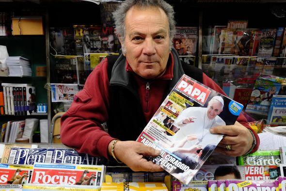Un vendedor de periódicos romano tiene la nueva revista italiana Il Mio...