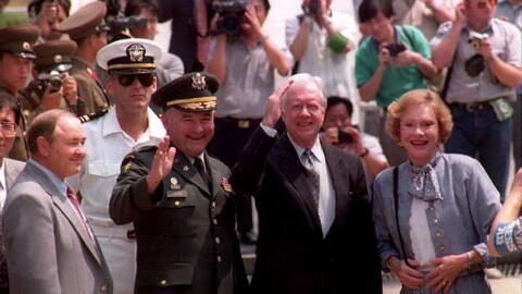 El expresidente Jimmy Carter saluda al cruzar la frontera entre Corea de...
