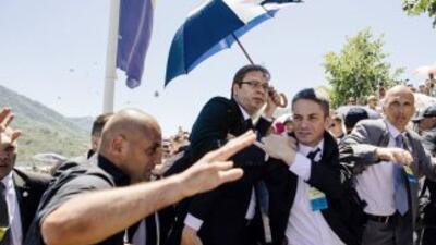El primer ministro serbio, Aleksandar Vucic, quien es cubierto por sus g...