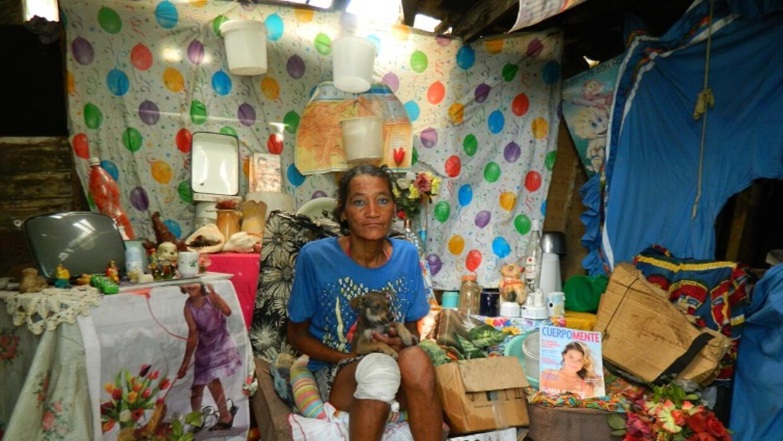 Luz María con su perro en la choza donde vive.
